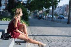 Donna bionda felice che si siede sui punti sulla via che indossa un rosso Fotografia Stock