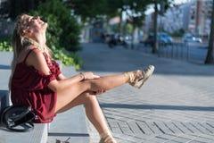 Donna bionda felice che si siede sui punti sulla via che indossa un rosso Fotografia Stock Libera da Diritti
