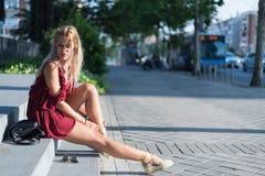 Donna bionda felice che si siede sui punti sulla via che indossa un rosso Fotografie Stock Libere da Diritti