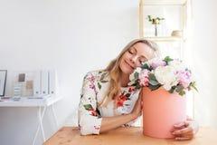 Donna bionda felice in un ufficio moderno con i fiori in un contenitore di cappello Mazzo dei peonies fotografie stock