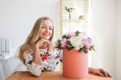 Donna bionda felice in un ufficio moderno con i fiori in un contenitore di cappello Mazzo dei peonies fotografia stock libera da diritti