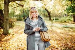 Donna bionda felice in una foresta o in un parco autunnale che manda un sms con il suo telefono cellulare Concetto di comunicazio immagini stock libere da diritti