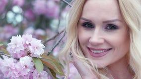 Donna bionda giovanile che posa con un albero rosa video d archivio