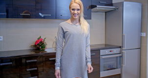 Donna bionda in Gray Dress Standing alla cucina video d archivio