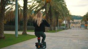 Donna bionda graziosa che conduce bici elettrica nel parco della città video d archivio