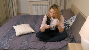 Donna bionda graziosa che indossa vestito convenzionale che si siede sul letto, smartphone di uso e bevente caffè Fotografie Stock Libere da Diritti