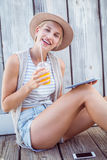 Donna bionda graziosa che per mezzo della sua compressa e tenendo succo d'arancia Fotografia Stock