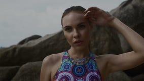 Donna bionda graziosa che riposa dopo la formazione fra le rocce vicino al mare durante il giorno di estate archivi video