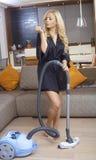 Donna bionda graziosa che usando l'aspirapolvere Fotografie Stock Libere da Diritti