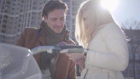 Donna bionda graziosa ed uomo bello alla via della città con la bicicletta che guarda nel telefono cellulare della signora Svago  archivi video