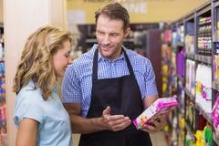 Donna bionda graziosa sorridente che parla con il venditore immagine stock