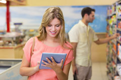 Donna bionda graziosa sorridente che per mezzo della compressa digitale e comprando i prodotti Fotografie Stock Libere da Diritti