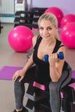 Donna bionda incinta sportiva che si esercita con le teste di legno su 9 mesi della gravidanza con piacere Immagine Stock