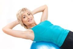 Donna bionda invecchiata sulla palla di forma fisica Fotografia Stock