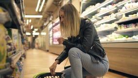 Donna bionda in jeans e bomber nero sugli edifici occupati che selezionano i prodotti a partire dagli scaffali più bassi e messi  archivi video