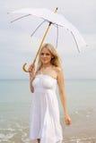 Donna bionda nel bianco sulla spiaggia Fotografia Stock