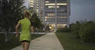 Donna bionda nell'addestramento corrente di usura di forma fisica sul passaggio pedonale del parco Posteriore dopo la vista Sera