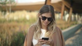 Donna bionda in occhiali da sole e cappotto che cammina nel parco e che sorride esaminando telefono stock footage