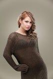 Donna bionda riccia che propone lavori o indumenti a maglia Immagine Stock Libera da Diritti