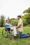 Donna bionda in sedia a rotelle con il partner che si inginocchia accanto lei Fotografie Stock