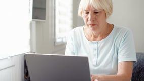 Donna bionda senior anziana che lavora al computer portatile a casa A distanza freelance il lavoro sul pensionamento stock footage