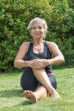 Donna bionda senior che fa il suo allungamento fuori verticalmente Fotografia Stock