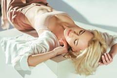 donna bionda sensuale in reggiseno rosa che si trova con gli occhi chiusi fotografie stock