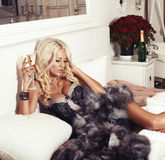 Donna bionda sexy in biancheria e pelliccia che si trovano sul letto con champagne Fotografia Stock Libera da Diritti
