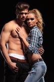 Donna bionda sexy che si appoggia il suo ragazzo topless Immagini Stock Libere da Diritti