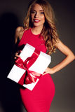 Donna bionda sexy che tiene una scatola con un regalo, posante nello studio Fotografie Stock