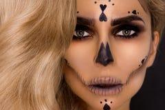Donna bionda sexy nel trucco di Halloween ed attrezzatura di cuoio su un fondo nero nello studio Scheletro, mostro immagini stock