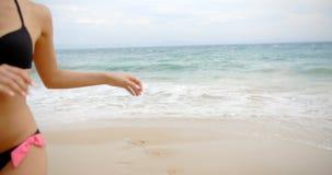 Donna bionda sorridente in bikini che cammina sulla spiaggia stock footage