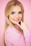 Donna bionda sorridente in camicia a quadretti rosa Fotografie Stock