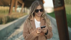 Donna bionda sorridente che cammina nel parco di autunno, esaminando smartphone e battitura a macchina archivi video