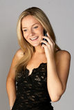 Donna bionda sorridente che comunica sul telefono delle cellule Immagine Stock Libera da Diritti