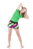 Donna bionda sorridente che dura in abiti sportivi che stanno con le gambe sulla larghezza della spalla che inclina al lato Immagini Stock Libere da Diritti