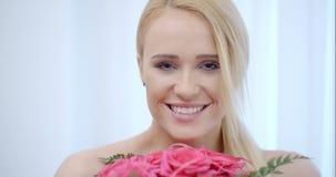 Donna bionda sorridente che odora le rose rosa video d archivio