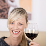 Donna bionda sorridente che tosta con un bicchiere di vino Immagine Stock