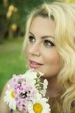 Donna bionda sorridente con i fiori immagine stock