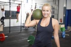 Donna bionda sorridente con la palla di colpo alla palestra di forma fisica Immagini Stock