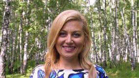 Donna bionda sorridente del ritratto nella fine del boschetto della betulla di estate su stock footage