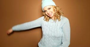 Donna bionda sorridente nel saltatore di inverno video d archivio