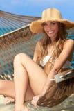 Donna bionda splendida che si rilassa in un'amaca Fotografia Stock Libera da Diritti