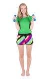 Donna bionda sportiva allegra che dura in abiti sportivi che tengono le teste di legno blu Fotografia Stock Libera da Diritti