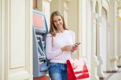 Donna bionda sui precedenti in BANCOMAT del centro commerciale immagini stock