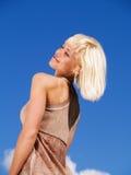 Donna bionda sul cielo blu pieno di sole Immagine Stock