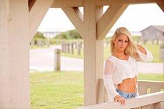 Donna bionda sul portico del paese fotografie stock libere da diritti