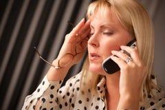 Donna bionda sul telefono delle cellule con lo sguardo sollecitato Immagine Stock Libera da Diritti