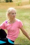Donna bionda sveglia che si rilassa dopo avere fatto un allenamento nel parco Fotografia Stock Libera da Diritti