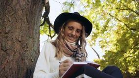 Donna bionda sveglia nel cappello che si siede vicino all'albero nel parco e che nota alcune idee in suo taccuino archivi video
